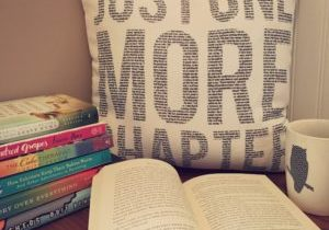 A stack of books, an open book, cup of coffee, and a bookish pillow are sitting on a bench.